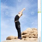 in the yoga pose Urdhva Hastasana or standing with arms raised pose ...