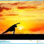 Yoga utthita parsvakonasana horizon pose by man silhouette at sunset ...