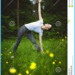 Yoga utthita trikonasana triangle pose by woman white costume on green ...