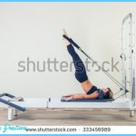 stock-photo-pilates-reformer-workout-exercises-woman-brunette-at-gym-indoor-333456989.jpg