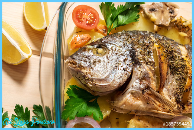 A delicious whole baked fish. Baked sea bream with lemon, onions